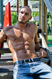 Bald young man shirtless outdoors sitting Royalty Free Stock Images