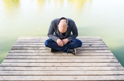 Bald young man sitting on the pier in the park and meditating. Horizontal portrait royalty free stock photo