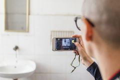 Bald Hispanic young woman taking photos with her cellphone in the washroom. Bald young woman taking photos with her cellphone of the old sing and mirror Royalty Free Stock Photography