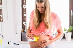 Bald-zu-ist die Mama, die für Haut am Bauch sich interessiert Stockbild