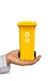 Balde do lixo do amarelo da oferta da mão Foto de Stock Royalty Free