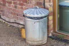 Balde do lixo velho do metal por uma parede de tijolo Foto de Stock