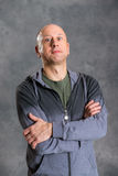 Baldheaded man with crossed arms in front of gray background Royalty Free Stock Photos