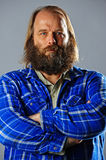 Balding bearded man with crossed arms. A balding bearded man wearing a plaid shirt crosses his arms as he looks into the camera Royalty Free Stock Photography