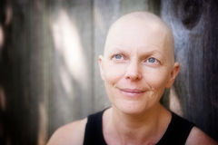 Balding cancer patient outside looking happy. Portrait of a woman balding from cancer treatment smiling and looking up royalty free stock images