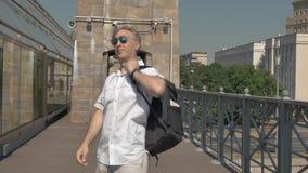 Balding de mens op middelbare leeftijd, op zonnebril zet, neemt een rugzak en gaat weg stock videobeelden