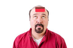 Balding man with a bank card on his forehead Stock Photo