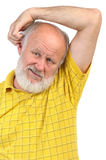 Balding senior man skratching his other ear. Balding senior man skratching his ear using opposite hand Royalty Free Stock Photo