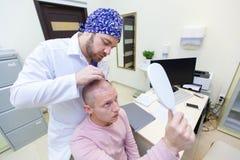 Baldness traktowanie Cierpliwy cierpienie od w?osianej straty w konsultacji z lekark? Przygotowanie dla w?osianego przeszczepu zdjęcia stock