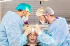 Baldness traktowanie W?osiany przeszczep Chirurdzy w sali operacyjnej wynosz? w?osian? przeszczep operacj? chirurgicznie obrazy royalty free