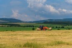 Bale сена трактора поднимаясь на кургане Стоковые Фото