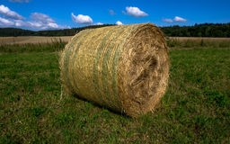 Bale of straw on the field - ready for pick up. A bale of straw after the harvest ready for pick up royalty free stock image