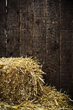 Bale of straw and wooden background. Bale of straw and dark wooden background with vignette Stock Image