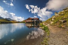 Balea glacier lake near the Transfagarasan road, panoramic view. Balea Lake, is a glacier lake situated at 2034m of altitude in the Fagaras Mountains, in Stock Photography