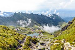 Balea Lake with clouds above. From top view. Bright blue sky on background. Rocks as leading lines. Fagaras Mountains, Romania royalty free stock photography