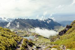 Balea Lake with clouds above. From top view. Bright blue sky on background. Rocks as leading lines. Fagaras Mountains, Romania stock photography