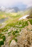 Balea lake in fog view from the top. Lovely summer landscape with low clouds around Royalty Free Stock Photo