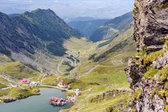 Balea Lake from top view. Balea Lake and serpentine road from top view. Cloudy sky on background. Fagaras Mountains, Romania royalty free stock photos