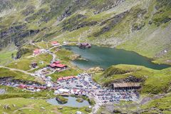 Balea Lake from top view. Traffic jams and parked cars. Sheeps on hill. Fagaras Mountains, Romania royalty free stock photography