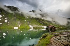 Balea sjö och Balea hotell i vårtid med moln Royaltyfri Bild