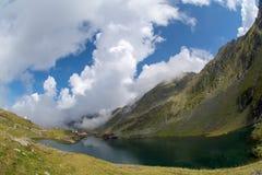 Balea sjö och Balea hotell i vårtid med moln Arkivbilder
