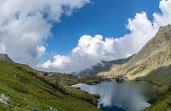 Balea sjö och Balea hotell i vårtid med moln arkivfoto
