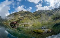 Balea sjö och Balea hotell i vårtid med moln Arkivbild
