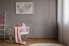 Baleine sur l'affiche sur le mur gris vide de l'intérieur mignon de chambre à coucher de bébé avec le berceau blanc avec la couve image libre de droits