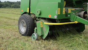 Baler discharge hay bale. Special press machine equipment eject discharge round fresh hay straw bale during agricultural harvesting in field stock footage