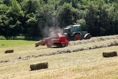 A baler in the fields during the harvesting process.  stock images