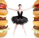 Balerina mince rejetant de grands hamburgers pour rester convenable Photographie stock