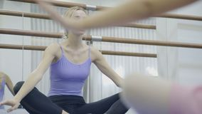 Balerina siedzi krzyż iść na piechotę i przedstawienia dlaczego zginać z ukosa z nastroszonymi rękami w balet klasie zbiory wideo