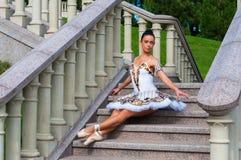 Balerina siedzi na schodkach, stoi w pointe pozyci Outdoors, wiosna fotografia royalty free