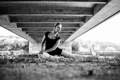 Balerina sitting under bridge looking over her shoulder Royalty Free Stock Photos