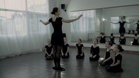 Balerina stojak przy przodem few mali balerinas które patrzeją ona Dorosła balerina uczy małym balerinas dlaczego ruszać się zbiory