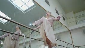 Balerina w beżowym sweatsuit i pointe rozciąga na barre w baletniczym gym Kobieta stoi blisko baru i lustra przygotowywa, zbiory