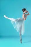 Balerina w bielu smokingowy pozować na palec u nogi, pracowniany tło fotografia royalty free