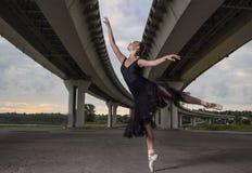 Balerina w czarnym stroju pozuje na palec u nogi, bridżowy tło zdjęcia royalty free