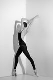 Balerina w czarnym stroju pozuje na pointe butach, pracowniany tło zdjęcie stock
