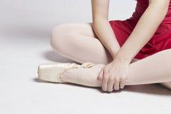 Baleriny obsiadanie na białej podłoga, dotyka jej stopę Fotografia Stock