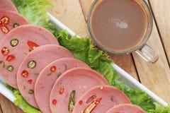 Baleron ciie w kółkowych dyski z czerwonymi pieprzami i gorącą kawą Zdjęcia Stock