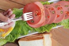 Baleron ciie w kółkowych dyski z czerwonymi pieprzami i gorącą kawą Fotografia Stock