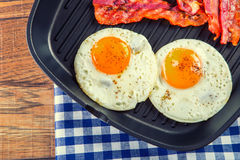 Baleron i Jajko Bekonowy i jajko Solony jajko i kropiący z czarnym pieprzem Piec na grillu bekon, dwa jajka w Teflon niecce obraz stock
