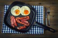 Baleron i Jajko Bekonowy i jajko Solony jajko i kropiący z czarnym pieprzem Piec na grillu bekon, dwa jajka w Teflon niecce Zdjęcie Stock