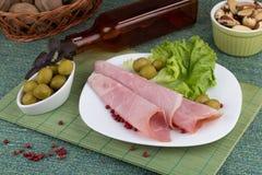 Baleron z zielonymi oliwkami i sałatką słuzyć na talerzu Zdjęcia Royalty Free