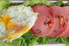 Baleronu cięcie w kółkowych dyski z czerwonymi pieprzami i jajkiem smażącymi. Zdjęcie Stock