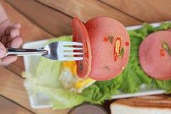 Baleronu cięcie w kółkowych dyski z czerwonymi pieprzami i jajkiem smażącymi. Zdjęcie Royalty Free