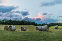 Bales of hay on rolling hill at storming sunset Stock Images