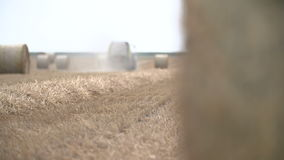 Bales of hay, tractor working in field stock footage