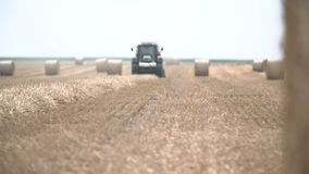 Bales of hay, tractor working in field stock video footage